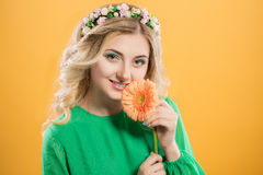 Beautiful blonde girl with a wreath on his head on yellow background. Woman holds gerbera flower near the face. Royalty Free Stock Photos