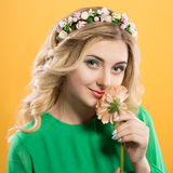 Beautiful blonde girl with a wreath on his head on yellow background. Woman holds gerbera flower near the face. Royalty Free Stock Photography