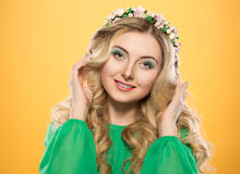 Beautiful blonde girl with a wreath on his head on yellow background. A woman holds a hand near the hair. Royalty Free Stock Photo