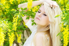 Beautiful blonde girl with yellow flowers Royalty Free Stock Image