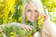 Beautiful blonde girl with yellow flowers Stock Image