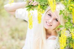 Beautiful blonde girl with yellow flowers Stock Photo