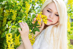 Beautiful blonde girl with yellow flowers Stock Photo