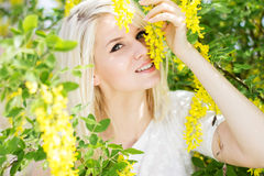 Beautiful blonde girl with yellow flowers Royalty Free Stock Images