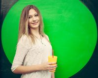 Beautiful blonde girl with a yellow glass in hand posing near the green wall. Outdoor Stock Image