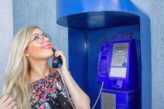 A beautiful blonde in glasses is holding a telephone receiver in a payphone. Beautifully smiling, looking at the sky and talking o. N the phone. It is royalty free stock photography