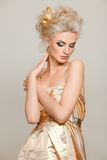 Beautiful blonde in gold dress Stock Photos