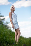 The beautiful blonde and grass. The blonde in a white dress costs in the field Stock Photo