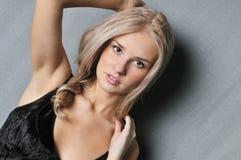 Beautiful blonde on a gray background. Portrait of beautiful girl on a gray background, looking at camera Stock Photo