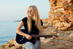 Beautiful blonde with a guitar on rock background Stock Photo