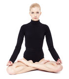 Beautiful blonde gymnast. Portrait of beautiful young blonde woman gymnast sitting in lotus pose Stock Photos
