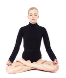 Beautiful blonde gymnast. Isolated portrait of beautiful young blonde woman gymnast sitting in lotus pose with eyes closed Royalty Free Stock Photos