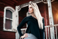 Beautiful blonde hair girl standing near red vintage house at sunset time Stock Photography