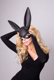 Beautiful blonde-haired young woman in carnival mask ballroom rabbit with long ears sensual sexy in a black dress, standing defian Royalty Free Stock Images
