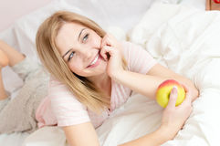 Beautiful blonde happy smiling young woman in bed with juicy apple in hands Royalty Free Stock Photos