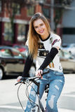 Beautiful blonde happy woman ride on the bicycle on city street Stock Image