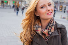 Beautiful blonde happy woman walking on the street in city. Outd Stock Image