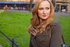 Beautiful blonde happy woman walking on the street in city. Outd Stock Photos