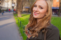 Beautiful blonde happy woman walking on the street in city. Outd Royalty Free Stock Photo