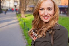 Beautiful blonde happy woman walking on the street in city. Outd Royalty Free Stock Image