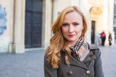 Beautiful blonde happy woman walking on the street in city. Outd Stock Photography