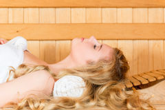 The beautiful blonde has a rest in a hot sauna. Eyes closed stock image