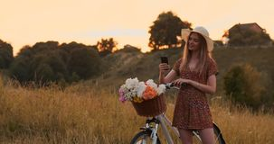 Beautiful blonde in a hat with a bike looking at the mobile phone screen and a basket on the handlebar with flowers. Beautiful blonde in a hat with a bike stock video footage