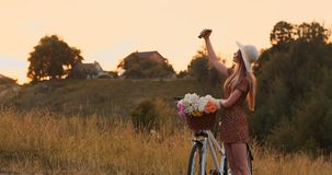 Beautiful blonde in a hat with a bike looking at the mobile phone screen and a basket on the handlebar with flowers. Beautiful blonde in a hat with a bike stock video