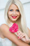 Beautiful blonde with a heart-shaped lollipop Royalty Free Stock Photos