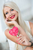 Beautiful blonde with a heart-shaped lollipop Stock Image