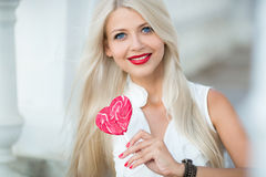 Beautiful blonde with a heart-shaped lollipop Royalty Free Stock Photography