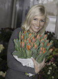 Blonde woman holding tulips Stock Photos