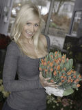 Blonde female holding tulips. Beautiful blonde holding a bouquet of red tulips in flower shop stock image