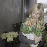 Blonde female holding tulips. Beautiful blonde holding a bouquet of red tulips while gazing away stock photo