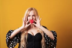 Beautiful blonde holding heart shaped cookie  on yellow background. Stock Photos