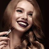 Beautiful blonde in a Hollywood manner with curls, dark lips, lipstick in hand. Beauty face and hair. royalty free stock photo