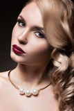 Beautiful blonde in a Hollywood manner with curls, red lips. Beauty face. Royalty Free Stock Image