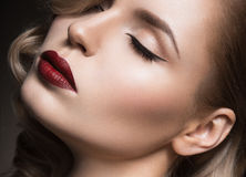 Beautiful blonde in a Hollywood manner with curls, red lips. Beauty face. Royalty Free Stock Images