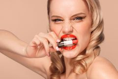 Beautiful blonde in a Hollywood manner with curls, red lips, lipstick in hand. Beauty face and hair. Cosmetology royalty free stock images