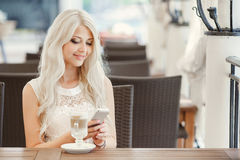 Beautiful blonde with a hot cup of coffee. Young women sitting in a cafe with a cup of cappuccino and is using a mobile phone Stock Photo