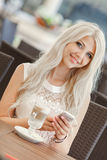 Beautiful blonde with a hot cup of coffee. Young women sitting in a cafe with a cup of cappuccino and is using a mobile phone Stock Images
