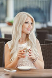 Beautiful blonde with a hot cup of coffee. Young women sitting in a cafe with a cup of cappuccino and is using a mobile phone Stock Photography