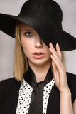 Beautiful blonde keeps hat one hand close eye Royalty Free Stock Photography