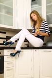 Beautiful blonde in the kitchen. Beautiful blonde in striped shirt and white jeans posing in the kitchen, she cut up lemon, fashion photography Royalty Free Stock Photos