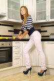 Beautiful blonde in the kitchen. Beautiful blonde in striped shirt and white jeans posing in the kitchen, she cut up lemon, fashion photography Stock Photos