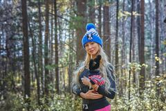 The beautiful blonde in a knitted cap walks with the dog in the autumn wood Royalty Free Stock Photography