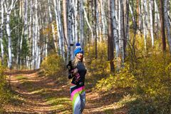 The beautiful blonde in a knitted cap walks with the dog in the autumn wood Royalty Free Stock Image