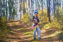 The beautiful blonde in a knitted cap walks with the dog in the autumn wood Stock Image
