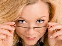 Beautiful Blonde Lady Looking Over her Glasses. A portrait of a beautiful blonde looking at the camera over her glasses Royalty Free Stock Photos