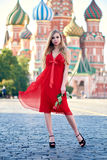 Beautiful blonde lady in red dress on Red Square Royalty Free Stock Photos